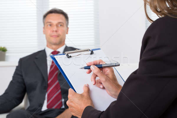 Psychiatrist Writing On Clipboard In Front Of Patient Stock photo © AndreyPopov