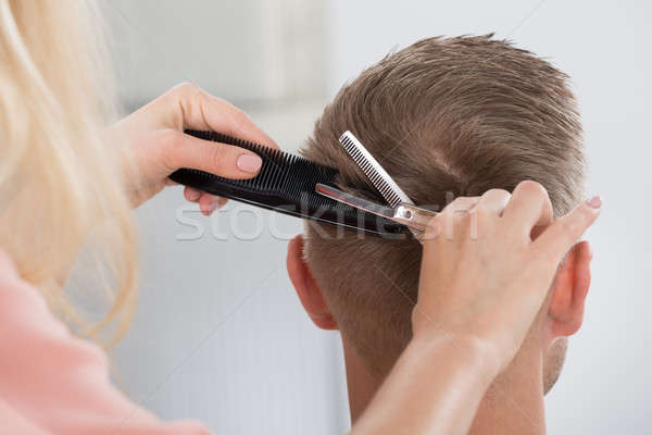 Man Getting Haircut From Female Hairdresser At Salon Stock photo © AndreyPopov
