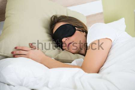 Woman Sleeping On Bed With An Eye Mask Stock photo © AndreyPopov