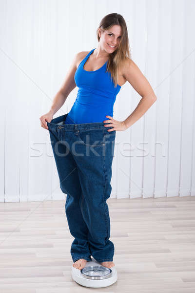 Woman In Oversized Jeans Standing On Weighing Machine Stock photo © AndreyPopov