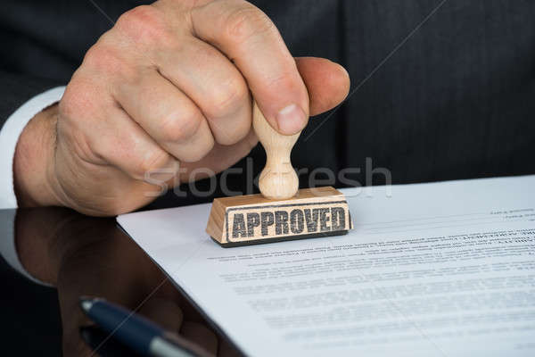 Close-up Of Businessman Hand Stamping On Approved Contract Form Stock photo © AndreyPopov