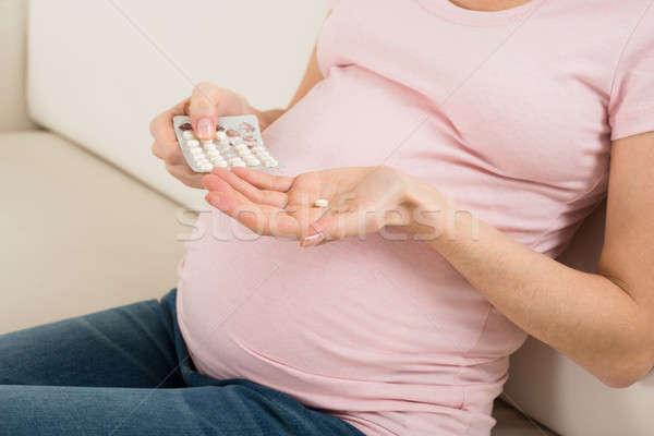 Pregnant Woman Taking Vitamin Pill Stock photo © AndreyPopov
