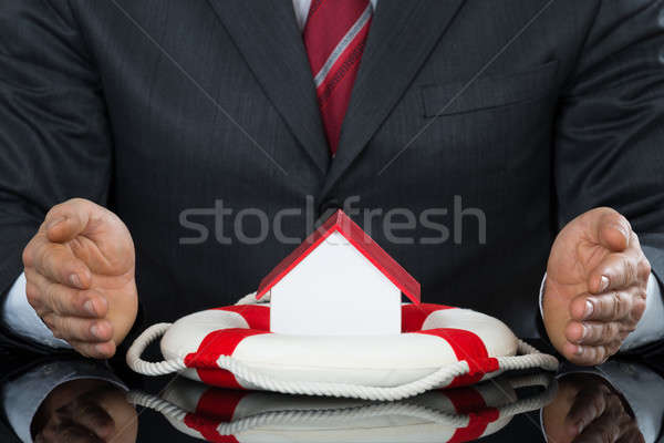 Businessman Hand Protecting House Model With Lifebelt Stock photo © AndreyPopov