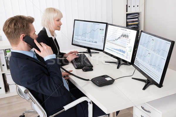 Two Businesspeople Analyzing Stock Charts Stock photo © AndreyPopov