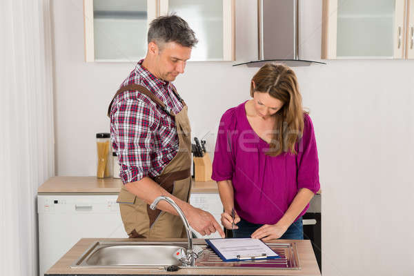 Woman And Male Plumber Signing Invoice Stock photo © AndreyPopov