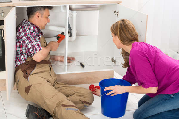 Stock photo: Male Plumber Repairing Pipe Under Sink In Kitchen