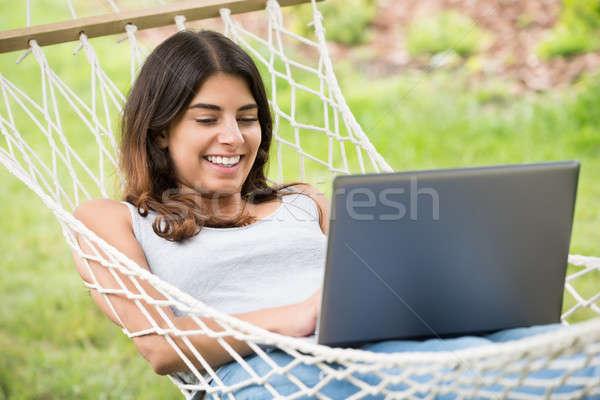 Nő függőágy laptopot használ mosolyog fiatal nő mosoly Stock fotó © AndreyPopov