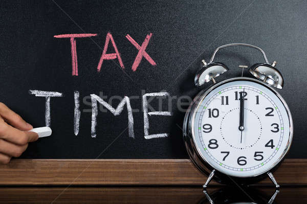 Stopwatch In Front Of Tax And Time Concept On Blackboard Stock photo © AndreyPopov