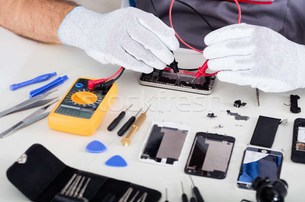 Person Checking Damaged Mobile Phone With Digital Multimeter Stock photo © AndreyPopov