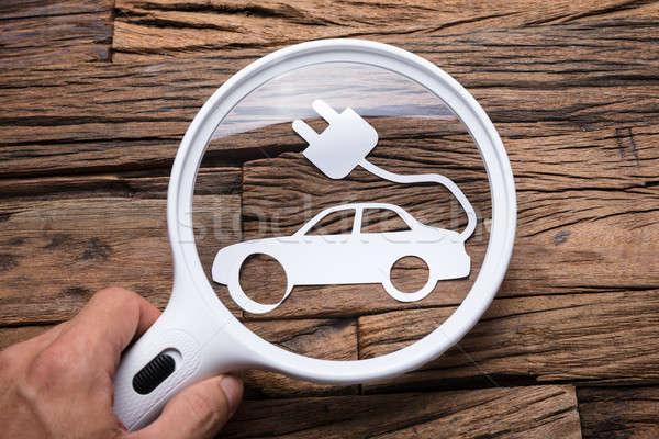 Mão lupa carro elétrico imagem mesa de madeira Foto stock © AndreyPopov