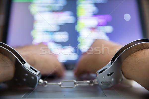 Person With Handcuff Using Laptop Stock photo © AndreyPopov