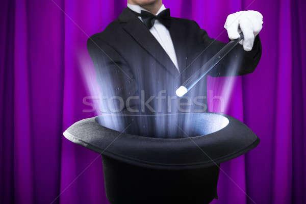Bűvész tart varázspálca megvilágított kalap közelkép Stock fotó © AndreyPopov