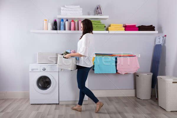 Kadın ayakta çamaşır makinesi sepet elbise gülen Stok fotoğraf © AndreyPopov