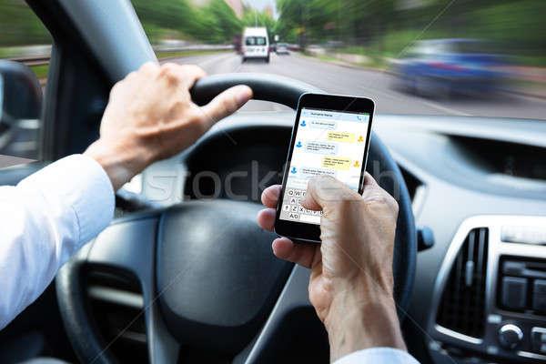 Férfi gépel szöveges üzenet mobiltelefon vezetés autó Stock fotó © AndreyPopov