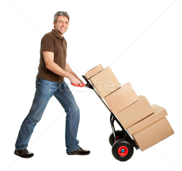 Delivery man pushing hand truck and stack of boxes Stock photo © AndreyPopov