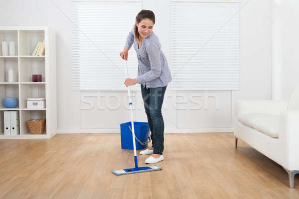 Woman Cleaning Hardwood Floor Of Living Room Stock photo © AndreyPopov
