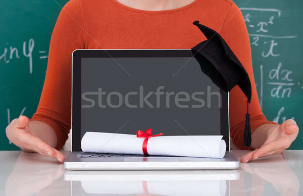 Student Showing Laptop With Mortarboard And Degree In Classroom Stock photo © AndreyPopov