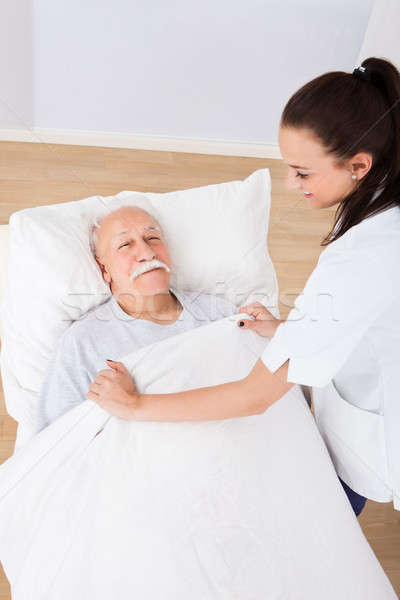 Doctor Covering Senior Man With Blanket Stock photo © AndreyPopov