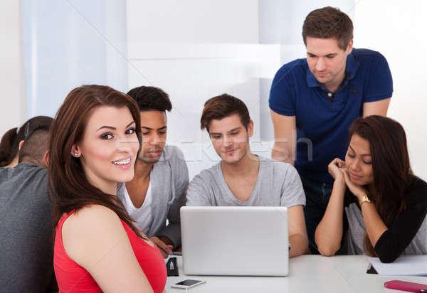 Gyönyörű egyetemi hallgató ül osztálytársak portré laptopot használ Stock fotó © AndreyPopov