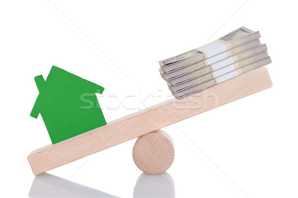 Green House Model And Dollar Bundles Balancing On Seesaw Stock photo © AndreyPopov