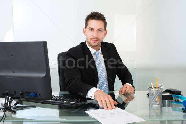 Confident Businessman With Document At Desk Stock photo © AndreyPopov