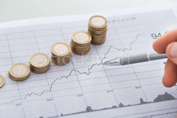 Hand With Pen Analyzing Line And Coin Graphs On Desk Stock photo © AndreyPopov