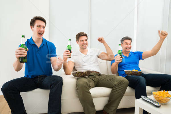 Men Holding Beer Bottles Cheering Stock photo © AndreyPopov