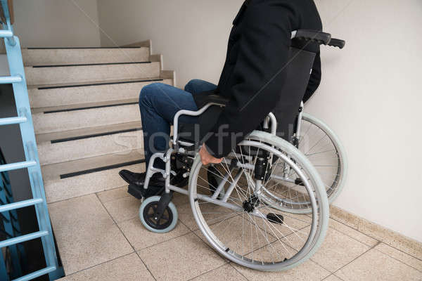 Man On Wheelchair In Front Of Staircase Stock photo © AndreyPopov