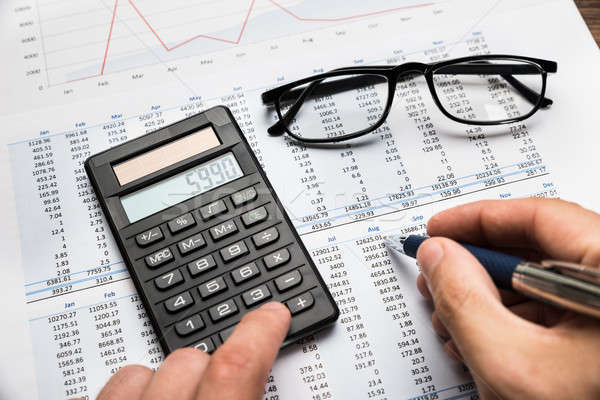 Businessman Calculating Financial Sheet Stock photo © AndreyPopov