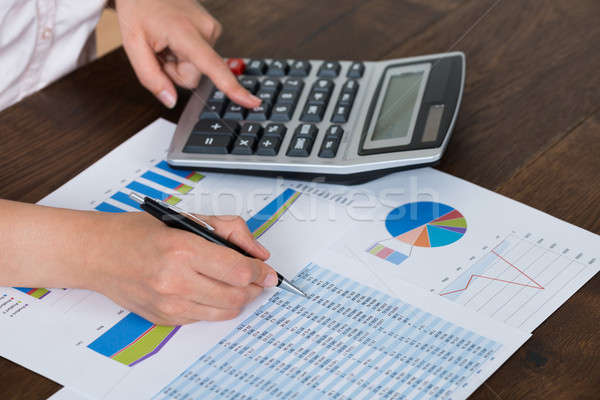 Businesswoman Analyzing Financial Report With Calculator Stock photo © AndreyPopov