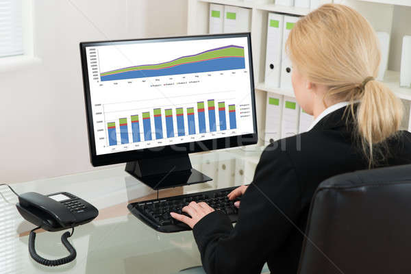 Businesswoman Analyzing Statistical Data On Computer Stock photo © AndreyPopov