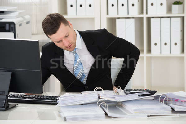 Businessman Suffering From Back Pain At Desk Stock photo © AndreyPopov