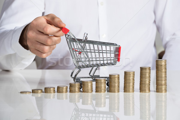 Businessman Holding Shopping Cart By Stacked Coins At Desk Stock photo © AndreyPopov