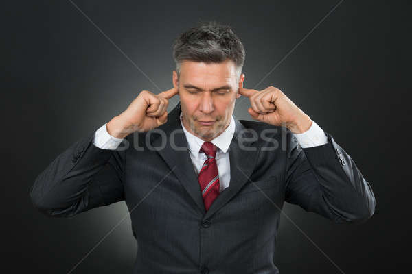 Businessman With Eyes Closed And Fingers In His Ears Stock photo © AndreyPopov