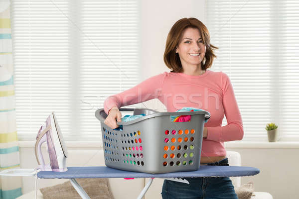 Woman With Iron And Basket Full Of Clothes Stock photo © AndreyPopov