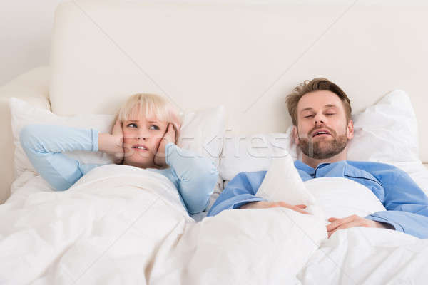 Woman Covering Ears While Man Snoring In Bed Stock photo © AndreyPopov