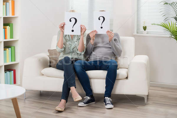 Couple Holding Question Mark Sign In Front Of Face Stock photo © AndreyPopov