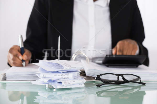 Close-up Of Businesswoman Calculating Tax On Desk Stock photo © AndreyPopov