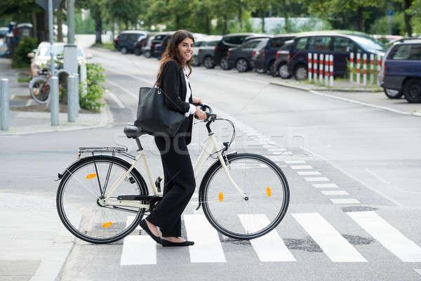 Sorridente empresária bolsa pendulares bicicleta vista lateral Foto stock © AndreyPopov