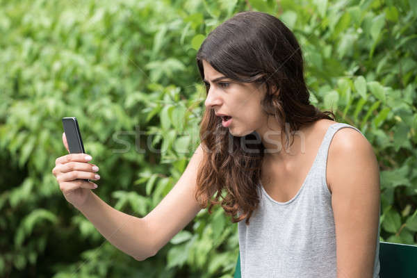 Frustrated Woman Looking At Mobile Phone Stock photo © AndreyPopov