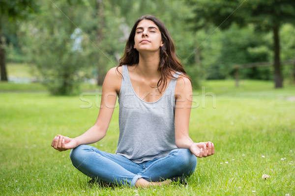 Nő meditáció park fiatal nő ül zöld fű Stock fotó © AndreyPopov