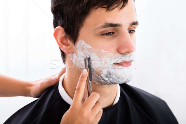 Hairdresser Shaving Man's Beard With Razor Stock photo © AndreyPopov