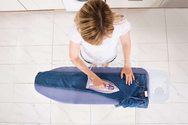 Stock photo: High Angle View Of Woman Ironing Jeans