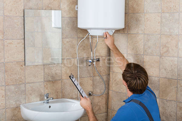 Male Plumber Holding Clipboard Checking Electric Boiler Stock photo © AndreyPopov