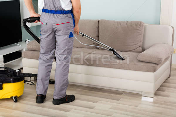 Male Worker Cleaning Sofa With Vacuum Cleaner Stock photo © AndreyPopov