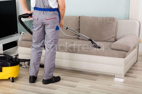 Férfi munkás takarítás kanapé porszívó hátsó nézet Stock fotó © AndreyPopov