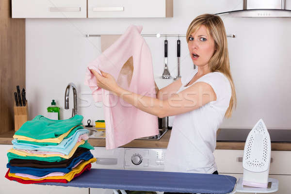 Shocked Woman Looking At Burnt T-shirt Stock photo © AndreyPopov