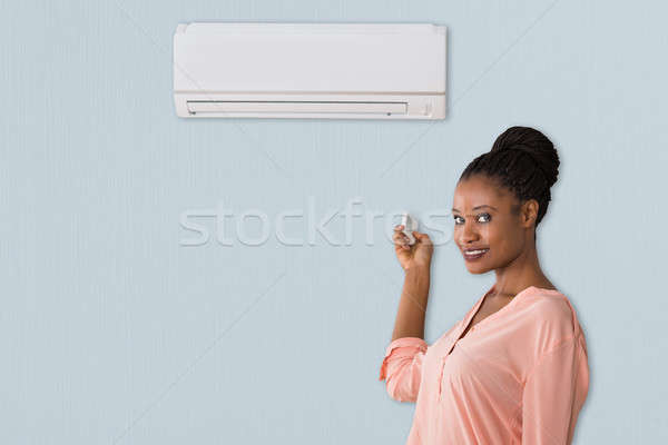 An African Woman Operating Air Conditioner Stock photo © AndreyPopov