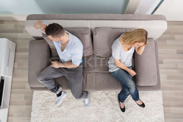 Upset Couple Sitting On Couch Stock photo © AndreyPopov
