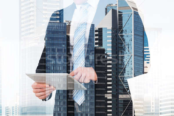 Businessman Using Digital Tablet Over Building Background Stock photo © AndreyPopov